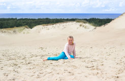Happy little baby girl enjoys sand playing in the dunes Stock Images