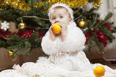 Happy little baby girl playing with fruits Stock Photo