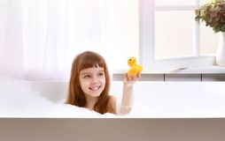 Happy little baby girl sitting in bath tub play with yellow duck toy in the bathroom. Happy little baby girl sitting in bath tub playing with yellow duck toy in stock photos