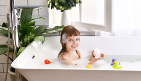 Happy little baby girl sitting in bath tub play with yellow duck toy in the bathroom Stock Photo