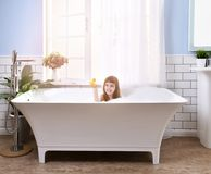 Happy little baby girl sitting in bath tub playing with duck toys in the bathroom stock images