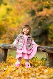Happy little baby girl sitting on a bench laughing and playing with leaves. In nature, walk in the open air.  Stock Image