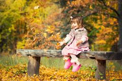 Happy little baby girl sitting on a bench laughing and playing with leaves. In nature, walk in the open air.  Royalty Free Stock Photography