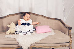 Happy little baby girl sitting on the couch with teddy bear toy. stock image