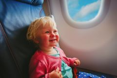 Happy little baby girl travel by plane. Happy little baby girl enjoy travel by plane stock photo