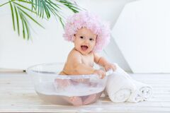 Happy little baby girl washes in a basin with foam and water in a bright room at home in a beautiful bathing cap made of flowers
