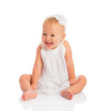 Happy little baby girl in white dress laughs isolated on white Royalty Free Stock Photo