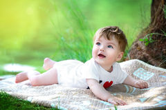 Happy little baby having fun in the park on the lake shore backg Stock Photo