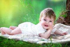 Happy little baby having fun in the park on the lake shore backg Stock Photos