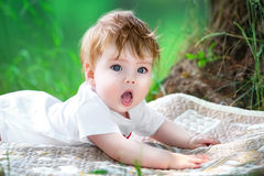 Happy little baby having fun in the park on the lake shore backg. Round. Summer vacations concept Royalty Free Stock Image