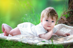 Happy little baby having fun in the park on the lake shore backg. Round. Summer vacations concept Royalty Free Stock Photography