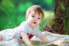 Happy little baby having fun in the park on the lake shore backg Royalty Free Stock Photos