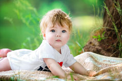 Happy little baby having fun in the park on the lake shore backg Royalty Free Stock Photo
