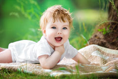 Happy little baby having fun in the park on the lake shore backg Royalty Free Stock Photography