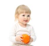 Happy little baby holding orange Royalty Free Stock Photos