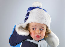 Happy little baby in a huge fur hat on white blackground Royalty Free Stock Photos