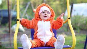 Happy little baby infant swinging on a swing. The girl is dressed in a cosplay fox costume. Pajamas called kigurumi.