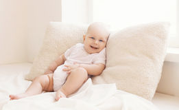 Happy little baby lying on the pillows at home in light Stock Images