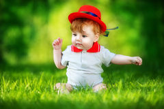 Happy little baby in red hat having fun in the park on solar gla Stock Photo