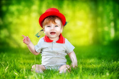 Happy little baby in red hat having fun in the park on solar gla Royalty Free Stock Images