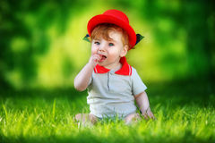 Happy little baby in red hat having fun in the park on solar gla Stock Image