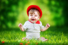 Happy little baby in red hat having fun in the park on solar gla Stock Photography