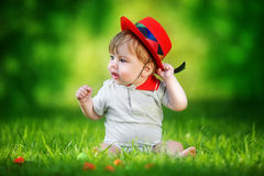 Happy little baby in red hat having fun in the park on solar gla. De. Summer vacations concept. The emotions Stock Photo