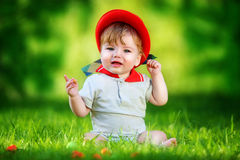 Happy little baby in red hat having fun in the park on solar gla Stock Images