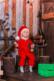 Happy little baby in Santa's costume near Xmas tree Royalty Free Stock Images