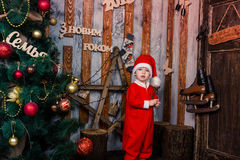 Happy little baby in Santas costume near Xmas tree Royalty Free Stock Photos