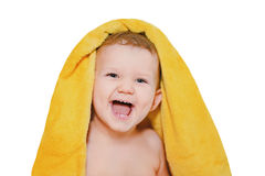 Happy little baby under a yellow towel isolated in white backgro Royalty Free Stock Photo