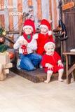 Happy little babys in Santa`s costumes near Xmas tree Royalty Free Stock Photography