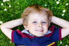 Happy little blond boy with blue eyes laying on the grass Stock Image