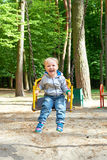 Happy little blond boy having fun on a swing. Stock Photography