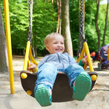 Happy little blond boy having fun on a swing. Stock Photos