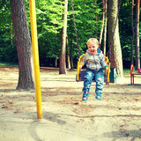 Happy little blond boy having fun on a swing. Royalty Free Stock Images