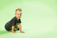 Happy little blond boy sitting, green bacground. Background Stock Photos