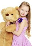 Beautiful little girl 5-6 years.She is holding a large teddy bea