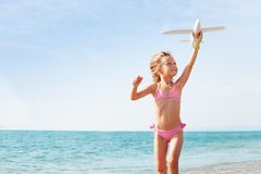 Happy girl playing with toy plane on the seashore royalty free stock images