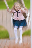 Happy little blond girl swinging Stock Image