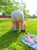 Happy little blond-haired boy with a blue net is upside down on a green lawn