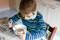 Happy little blond kid boy eating cereals for breakfast or lunch. Healthy eating for children. Royalty Free Stock Photos
