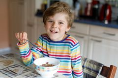 Happy little blond kid boy eating cereals for breakfast or lunch. Healthy eating for children. Royalty Free Stock Photo
