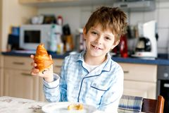 Happy little blond kid boy eating fresh croissant for breakfast or lunch. Healthy eating for children. Child in colorful pajama sitting in domestic kitchen royalty free stock images