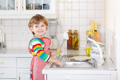 Happy little blond kid boy washing dishes in domestic kitchen. Adorable happy little blond kid boy washing dishes in domestic kitchen. Child having fun with Stock Images