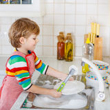Happy little blond kid boy washing dishes in domestic kitchen Royalty Free Stock Images