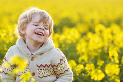 Happy little blond toddler boy lauging in yellow rape field on a Royalty Free Stock Image