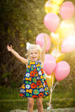 Happy little blonde caucasian girl outside with balloons royalty free stock images
