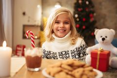 Happy little blonde girl with candy cane looking at camera while. Sitting at festive table Stock Images