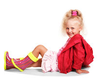 Happy little blonde girl in jacket , rubber boots, skirt isolated. Happy little blonde girl in a red jacket and colorful rubber boots, a pink skirt sitting Stock Image